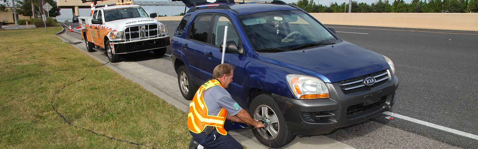 Road Ranger roadside assistance fixing a tire along expressway