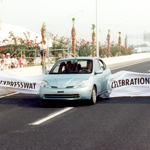 Car drives through banner at Central Florida Expressway toll road 429 ribbon cutting ceremony