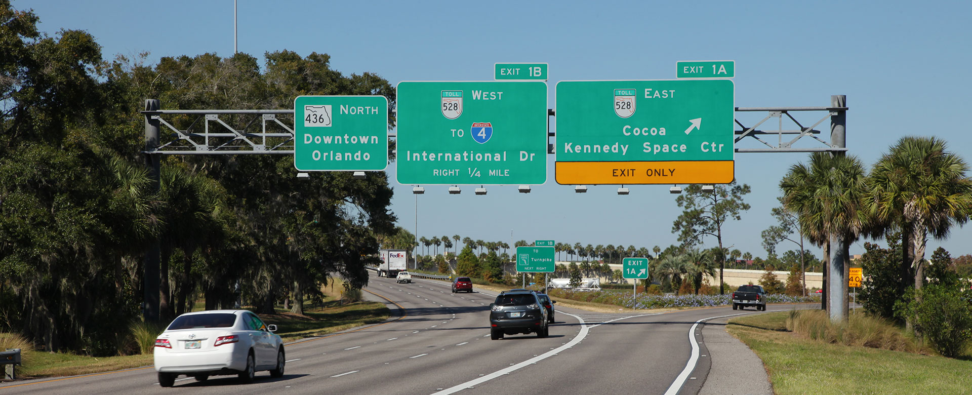 Road signs at exit from Orlando International Airport to state road 436 North, toll road 528 West to Interstate 4 and International Drive, and toll road 528 East to Cocoa Beach Kennedy Space Center