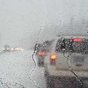 Winter traffic jam seen through a wet windshield