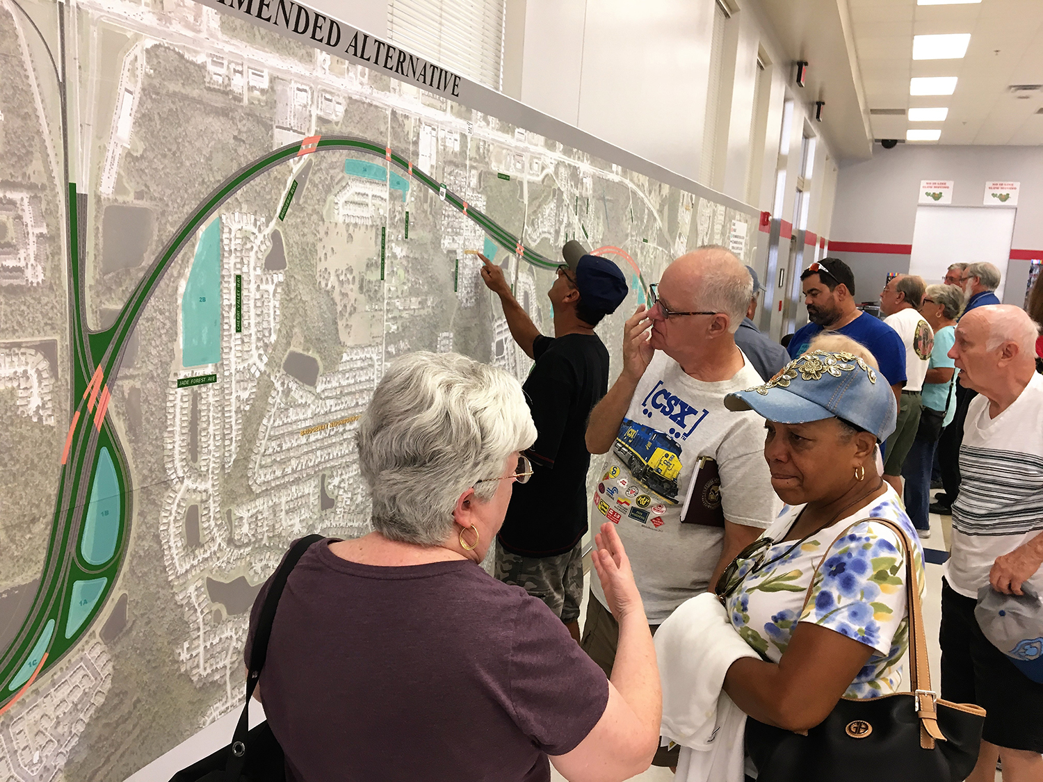 Citizens study maps of the PD&E Study for State Road 408 Eastern Extension during a public meeting